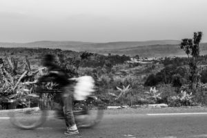 A man carries goods up the hill towards the Tutsi refugee camp, in the distance the original commune of Ruhuroro is visible where thousands of Tutsi were assembled before being killed.