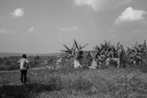 A man looks over the communal land where Tutis used to live and work. The Tutsi owned house that was destroyed has since been overtaken by local Hutu farmers.
