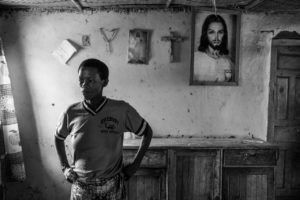 A Tutsi woman stands in her home built on communal land. She is one of a few Tutsis who have moved back to the communal land, largely for economic reasons.