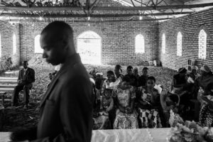 The pastor of a Hutu church in the commune prays over his congregation. A few Tutsi have joined the church but divisions in the village still run deep.