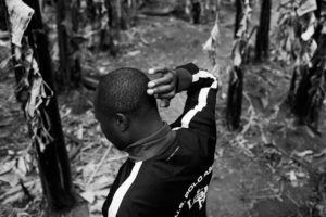 A Hutu man shows the location where a relative was killed, indicating the place on the skull where Tutsis killed his uncle with a club.